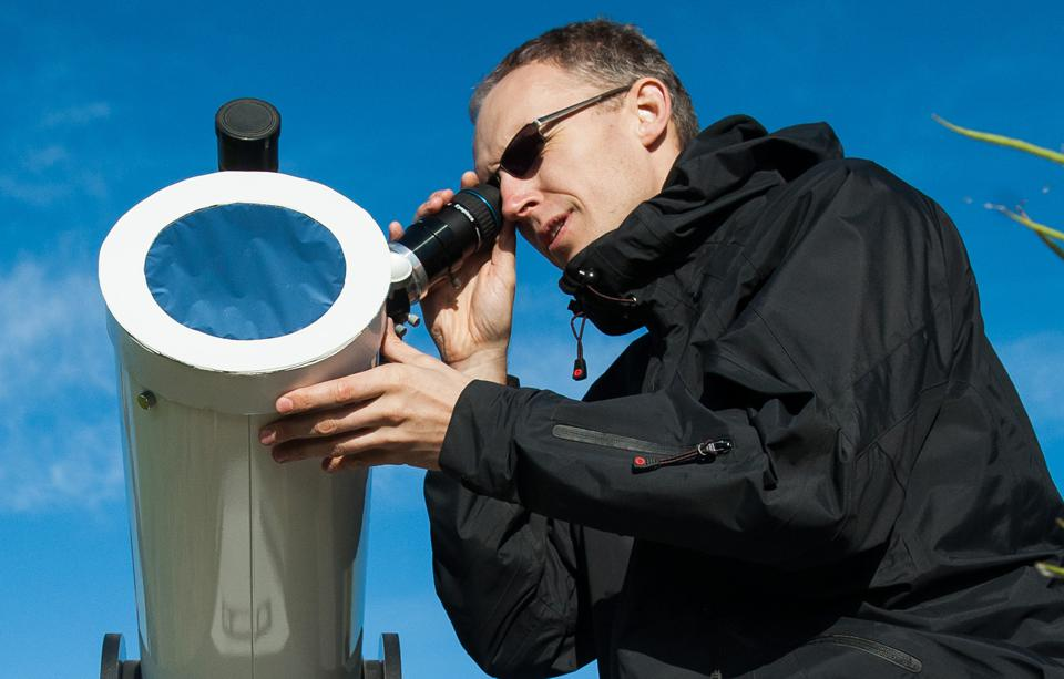 A man looks through a telescope early on
