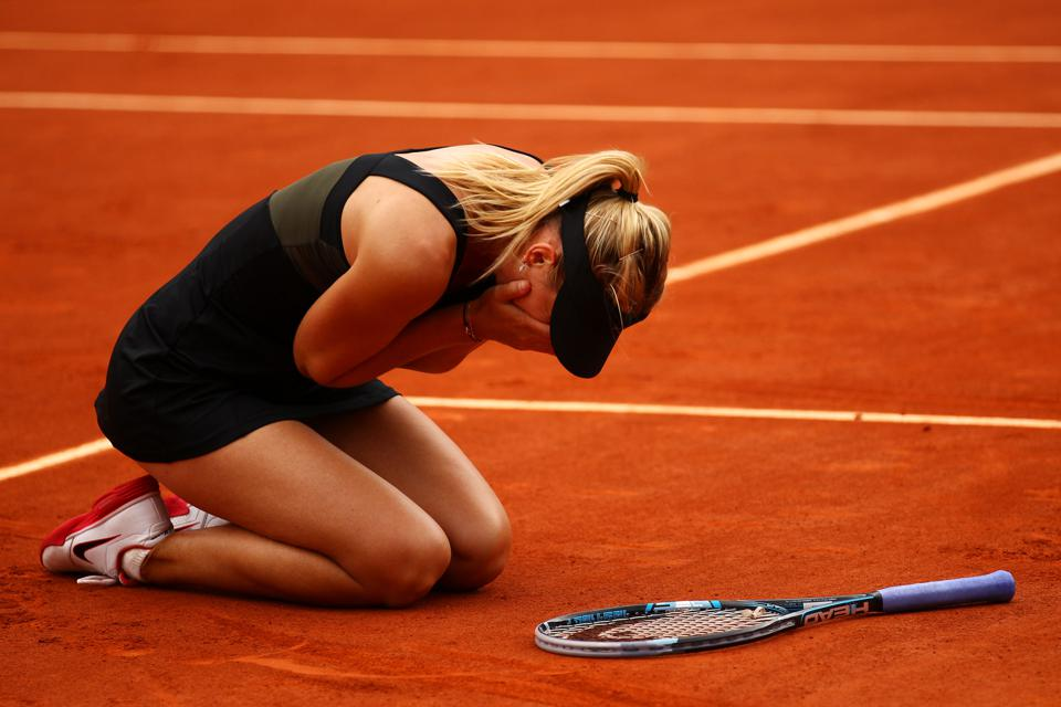 Maria Sharapova sinks to the clay after winning the 2012 French Open title.