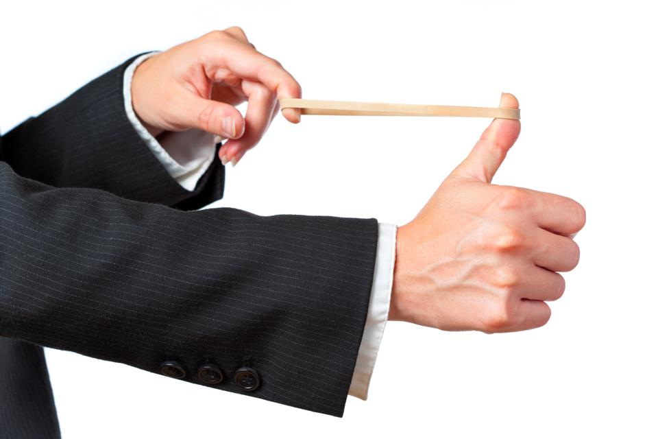 A businessman aiming a rubber band on a white background