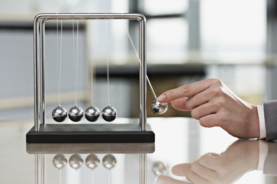 Close up of businesswoman's hands playing with Newton's cradle