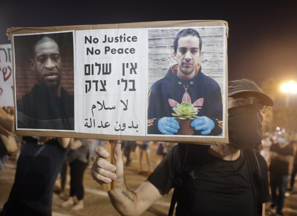 A protestor holds a placard with a picture of George Floyd and Eyad Hallaq with the words ″no justice, no peace″ in English and Arabic