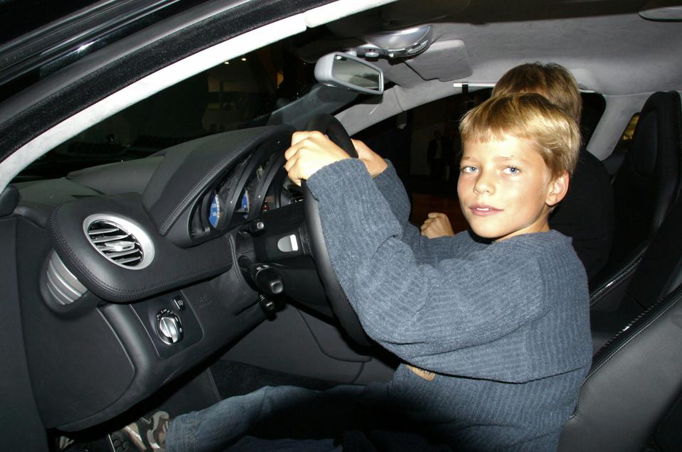 Teenager sitting at the steering wheel of a Mercedes - Benz SLR McLaren sports car.