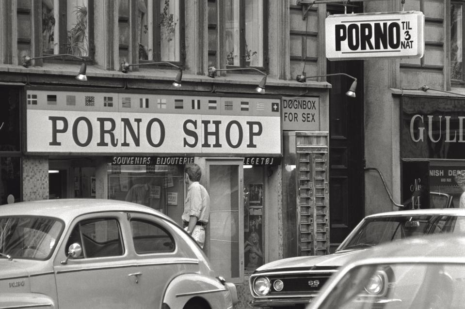 A man is observing the window of a porn shop