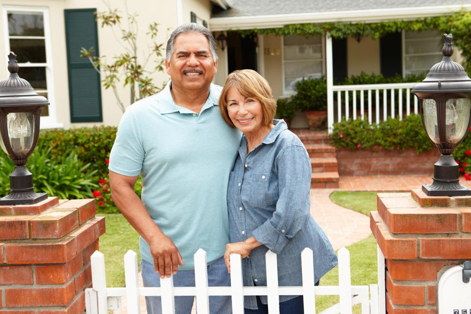 Retiree couple standing outside home