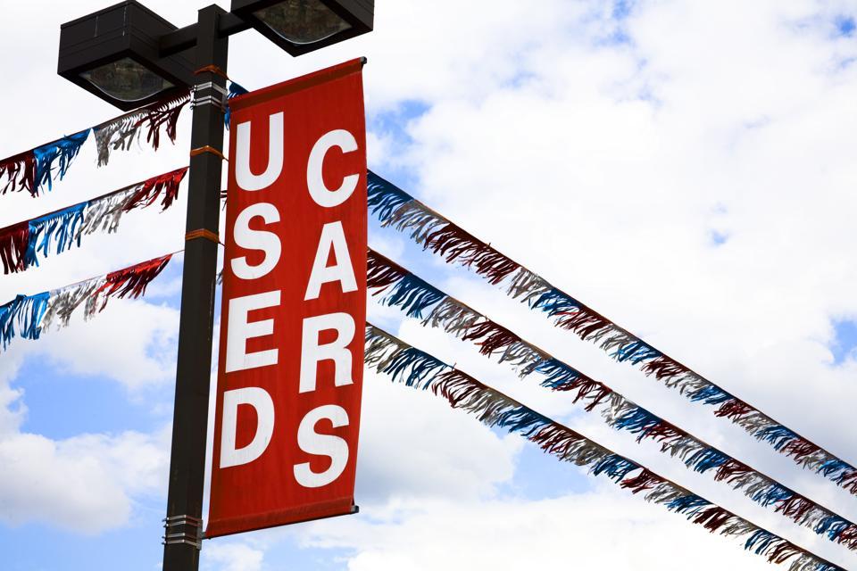Transportation:  'Used Cars' sign over a dealership car lot.