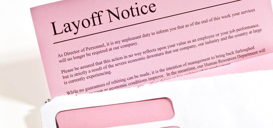 Close-up of layoff notice or pink slip in opened envelope.