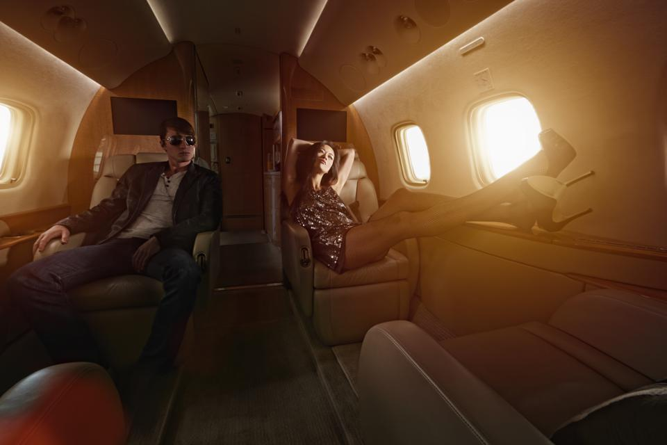 Young couple flying on private jet.