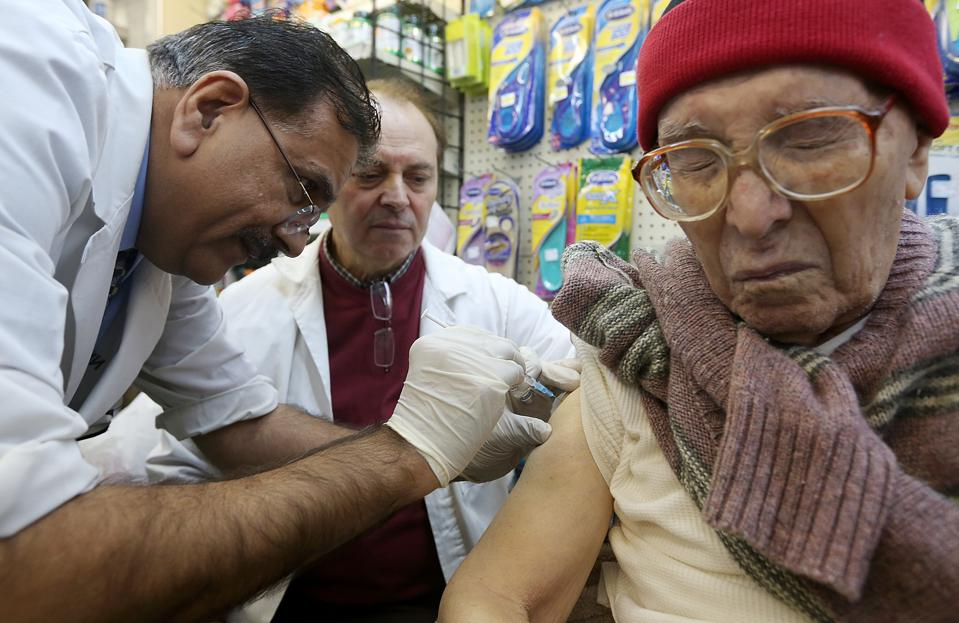 An elderly woman receives a flu vaccination from two medical technicians.