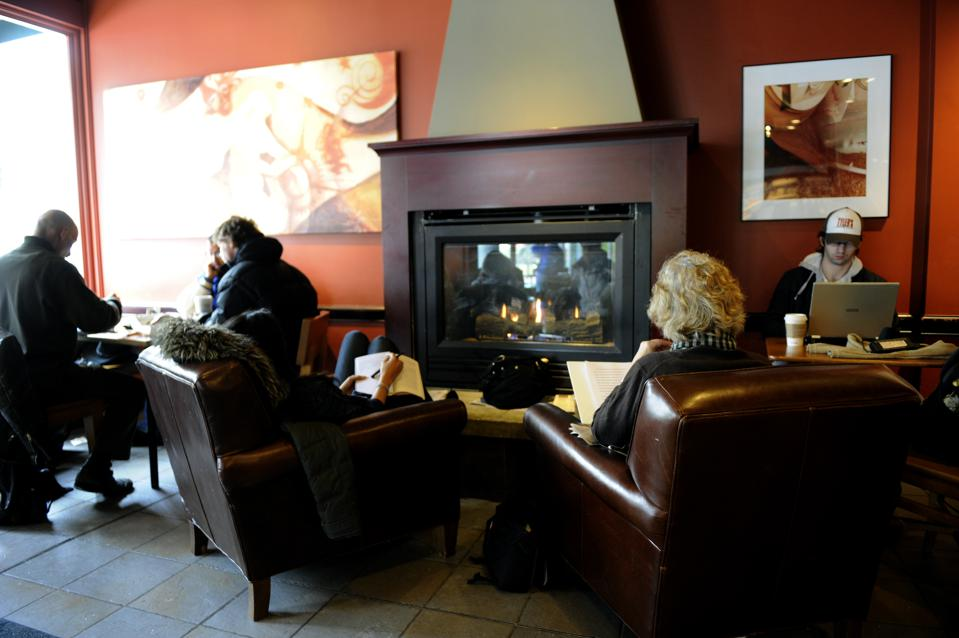 Customers at a local coffee shop on Boulder's Pearl street mall gatehr around the fire to keep warm, enjoy a warm drink and catch up on some reading and work. Cold weather is beginning it's wintery grip on Colorado as a low pressure system brings in frigi