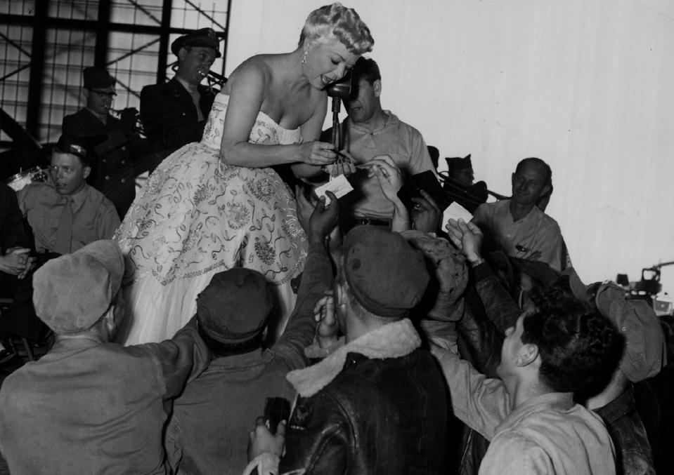 Frances Langford signs entertains and signs autographs for troops at a USO tour during World War II.