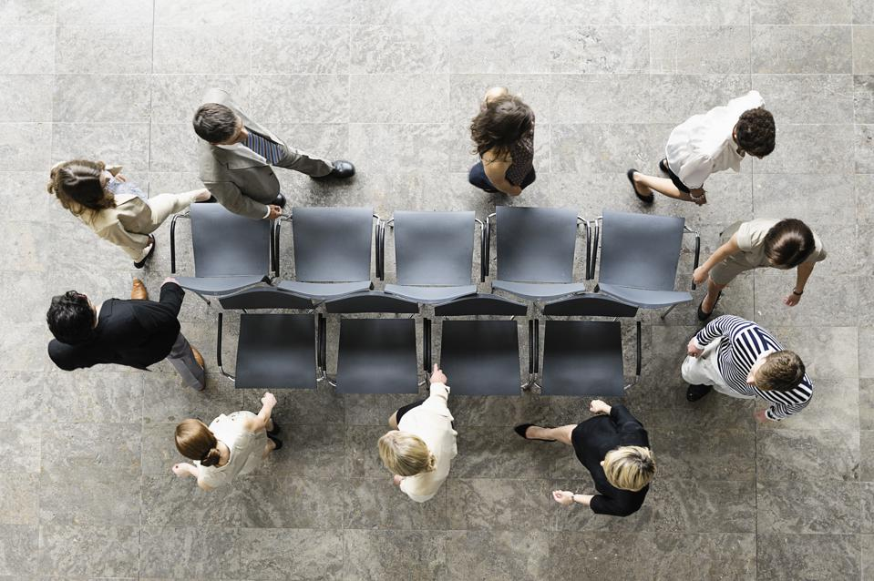 Business people playing musical chairs