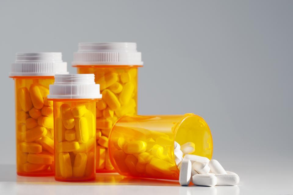 Four full prescription bottles with one spilling medication