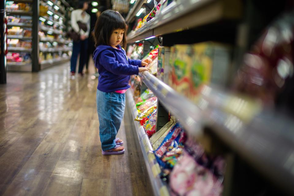 Toddler girl looking at candies on candy rack