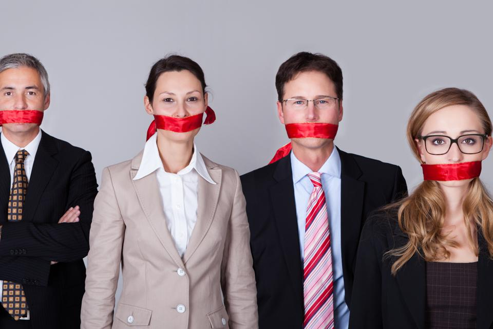 Four businesspeople with red tape around their mouths