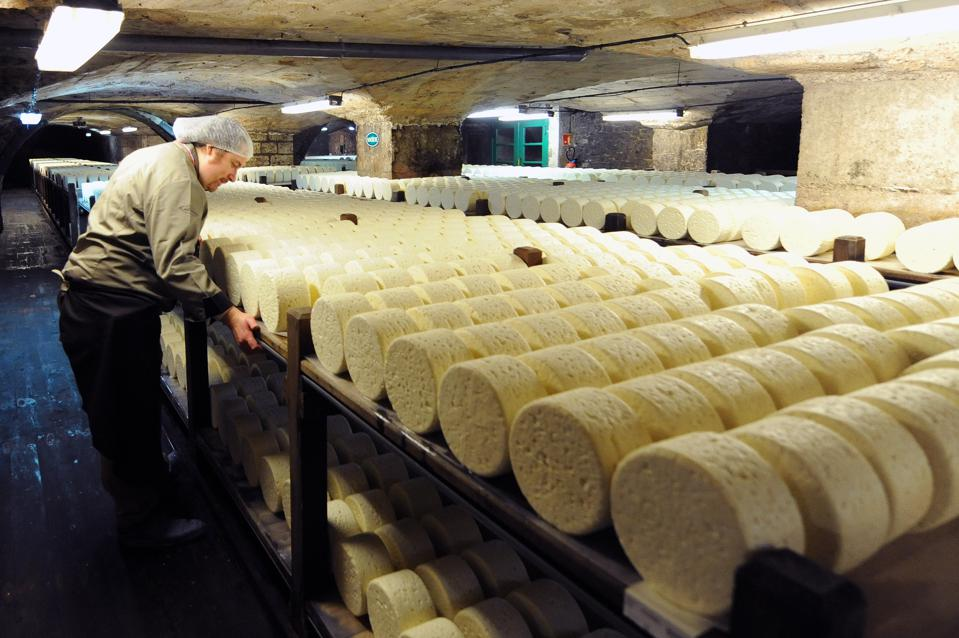 A cheesemaker looks at cheeses at the Roquefort Societé on May 16, 2013 in a cellar at Roquefort-sur-Soulzon, southern France.