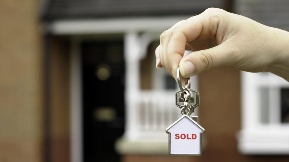 New home: female hand holding keys to a ″sold″ home