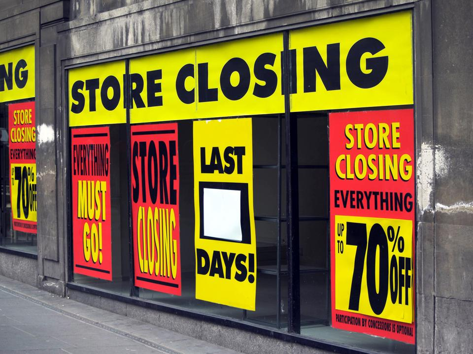 Store Closing and discount signs in department store windows
