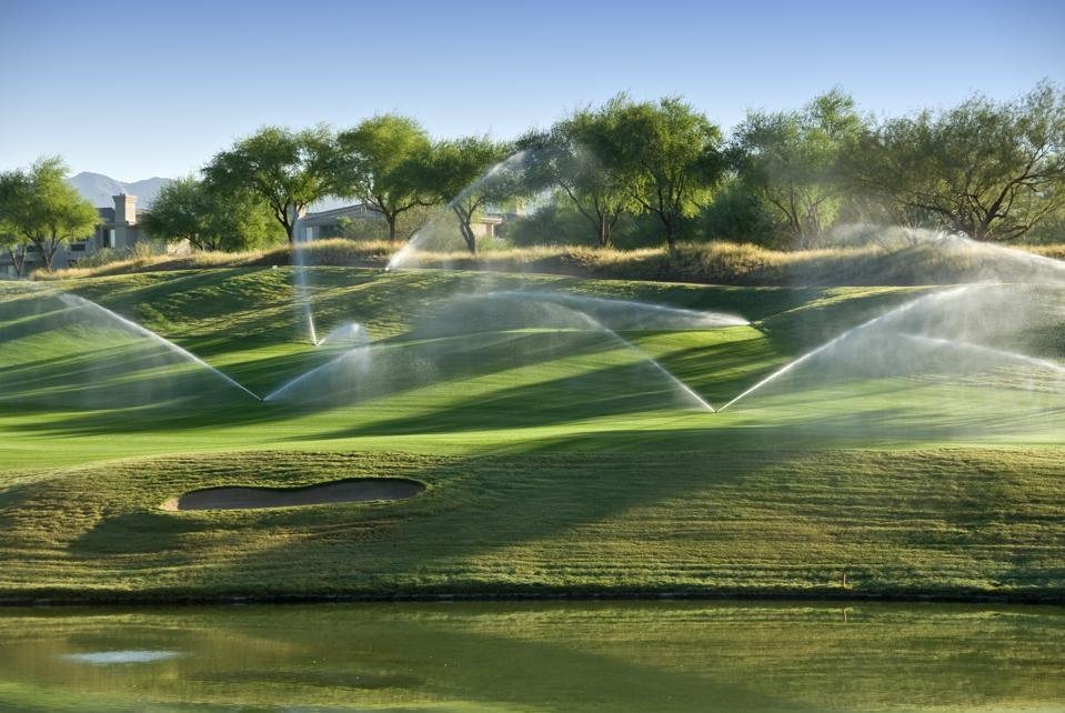 Lush green gold course in Arizona with sprinklers going off