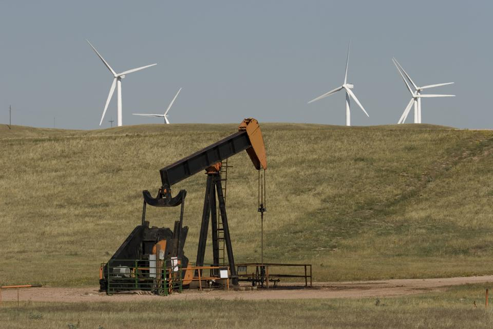 Wind turbines on the march near an aging pumpjack on the Colorado and Wyoming border.