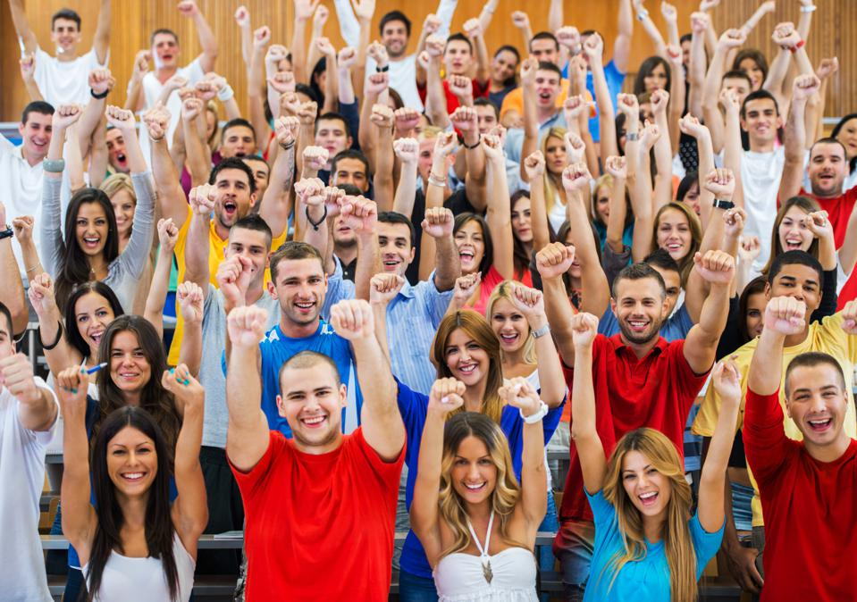 Successful students standing with raised arms.
