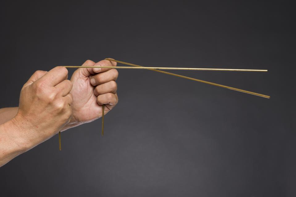 Two hands holding a pair of golden dowsing rods