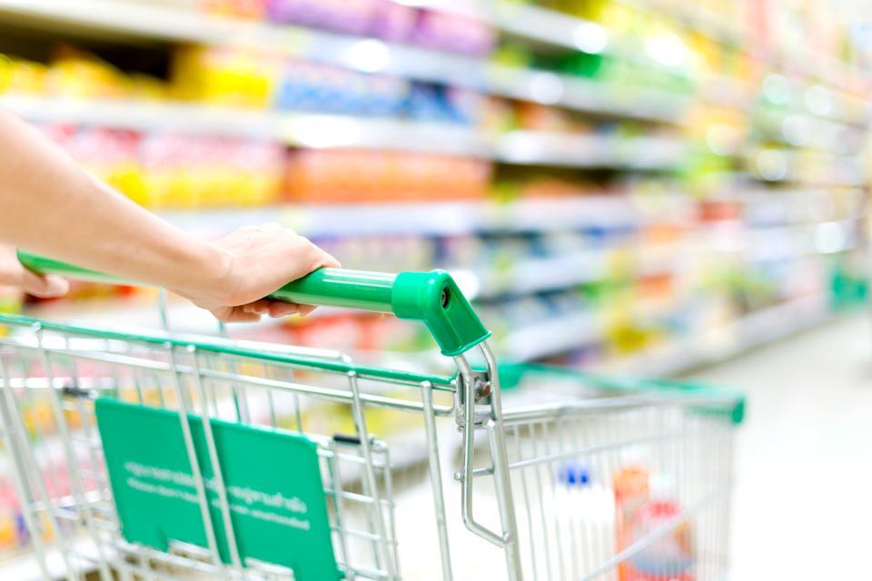 A grocery shopper pushes a shopping cart down a store aisle