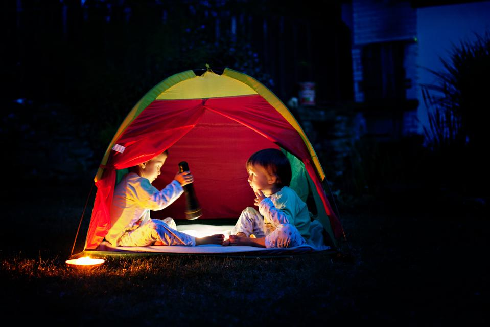 Two boys in a tent at night, reading a book