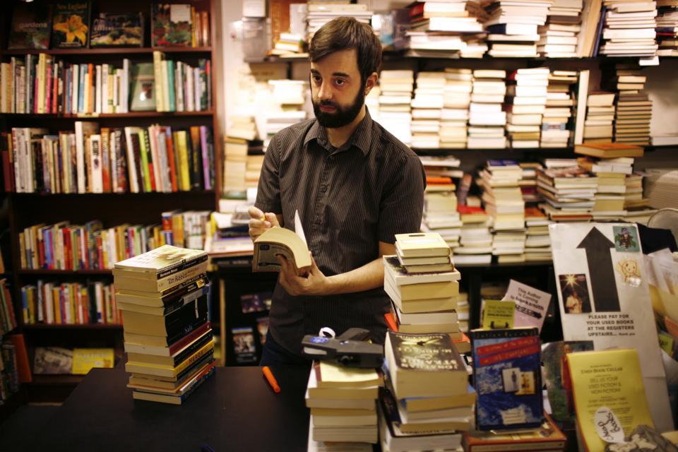 a male sorts books in a bookstore