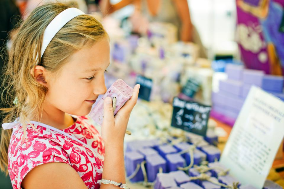 Child sniffing handmade soap at a farmer's market