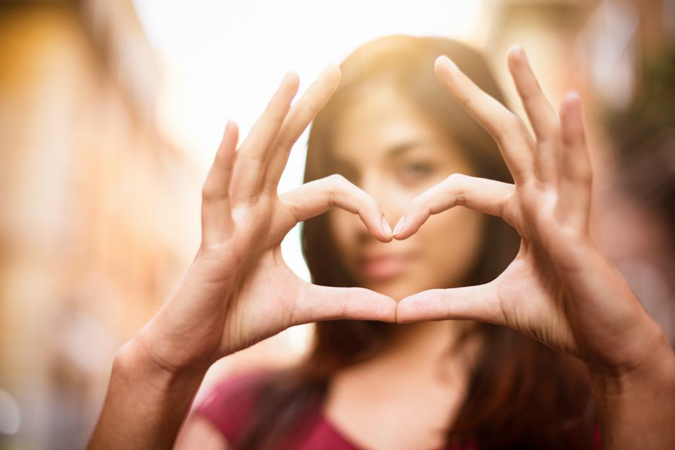 Close-up of woman making a heart shape with hands