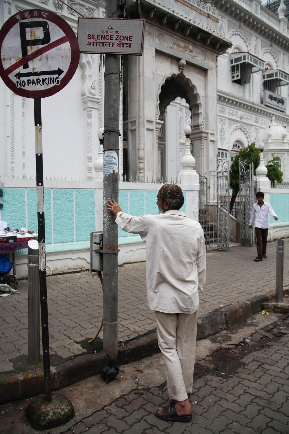 ″Silence zone″ and ″no parking″ signs, plus two men, outside a white mosque
