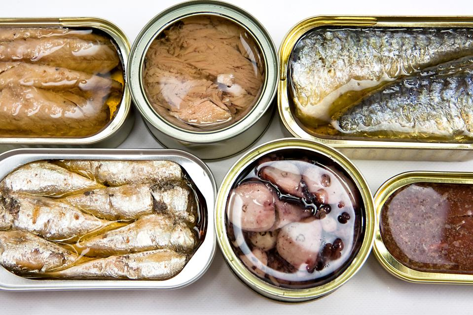 Tin cans full of seafood type foods like tuna and sardines