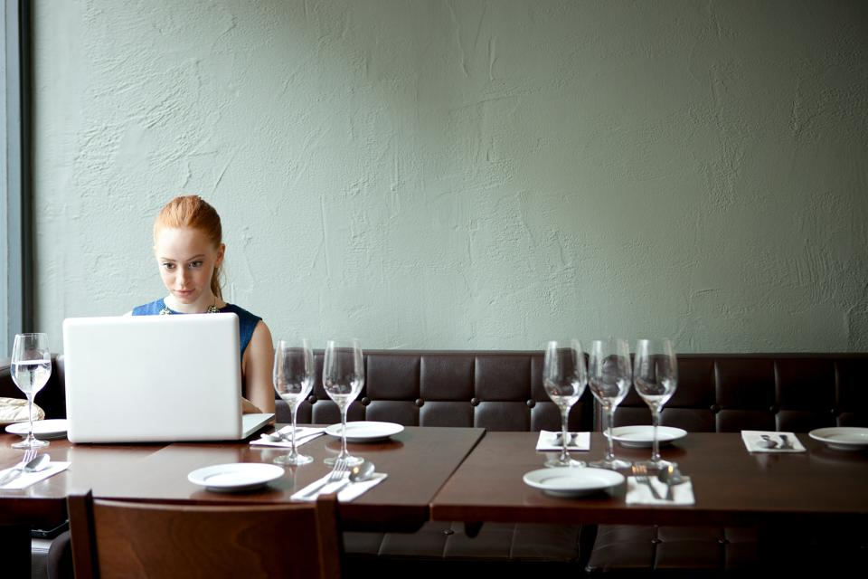 Young woman using laptop in restaurant