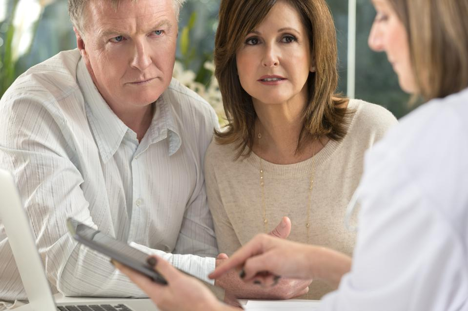 Worried mature couple with doctor using digital tablet.