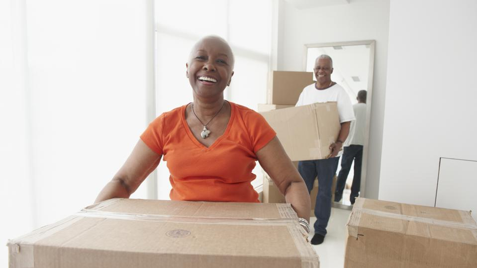 Senior Black couple carrying moving boxes in new home