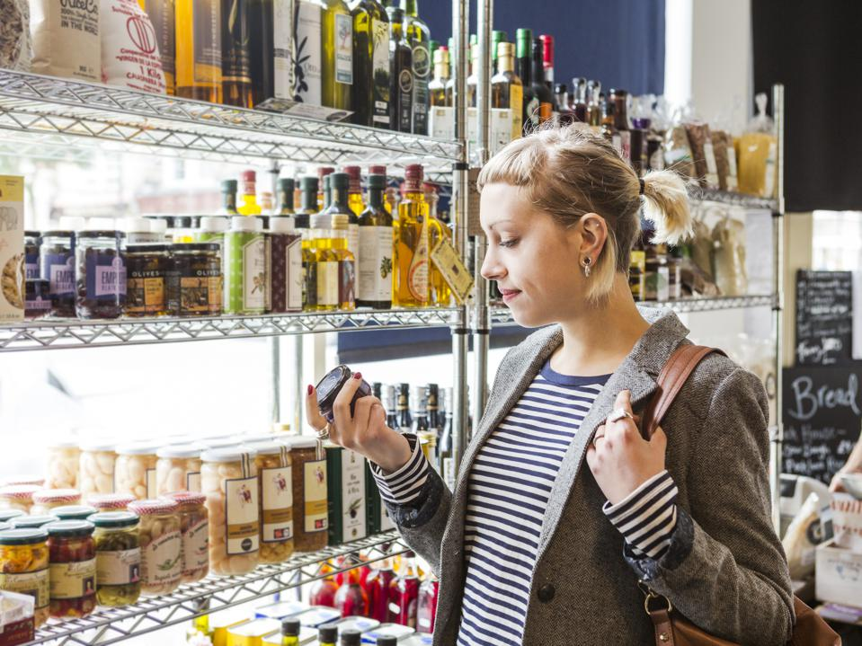 Female shopper reads label of jar in shop
