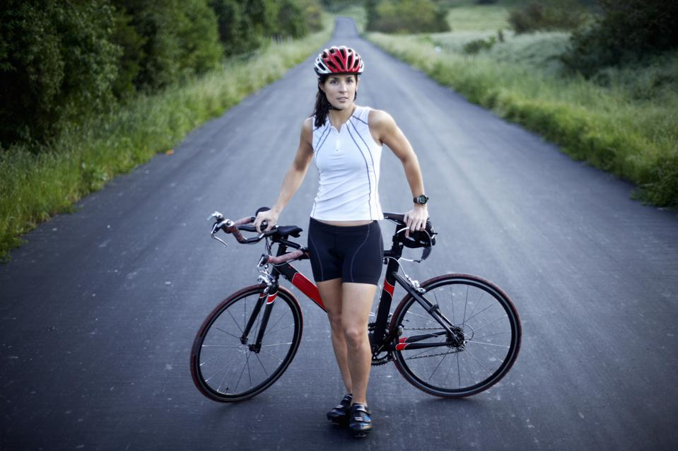 Female cyclist standing next to bicycle, portrait