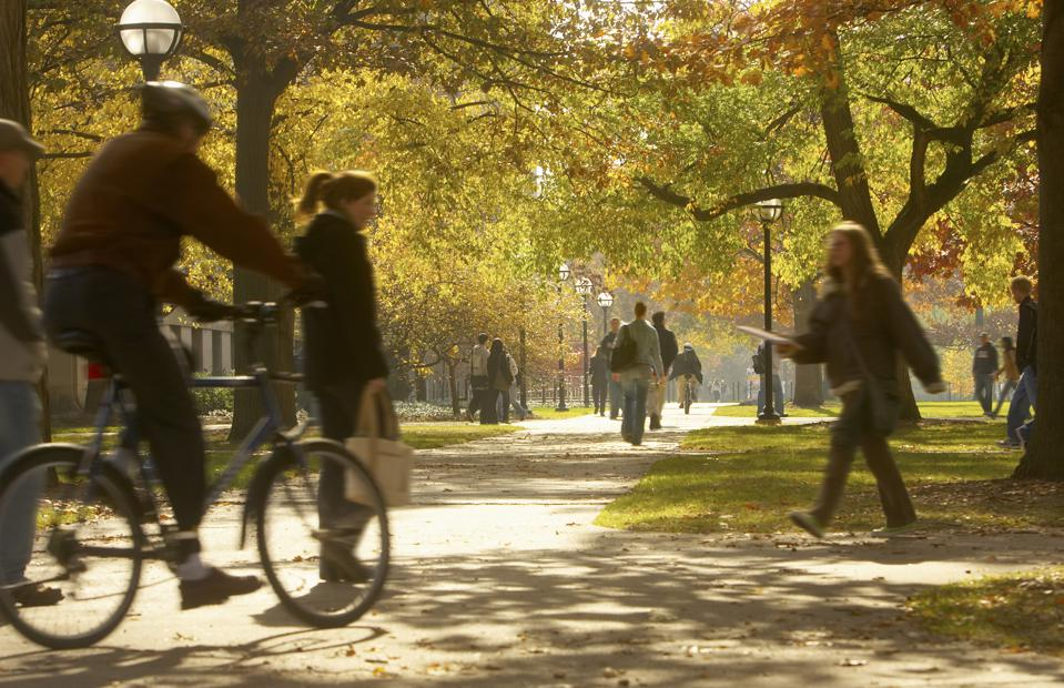 Students walking on footpaths on college campus, autumn
