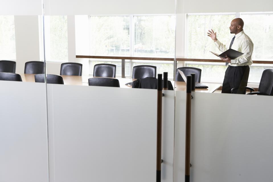 Businessman practicing presentation in boardroom, side view