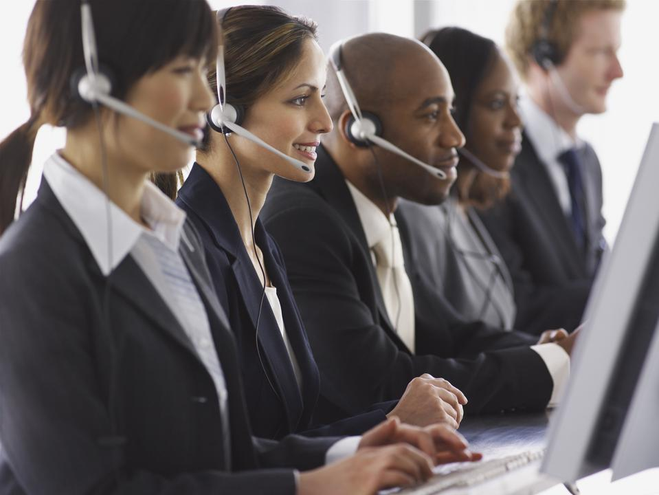 Row of businesspeople wearing headsets, close up