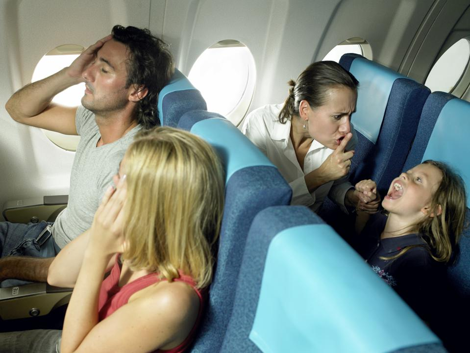 Girl (5-7) yelling behind young couple in airplane