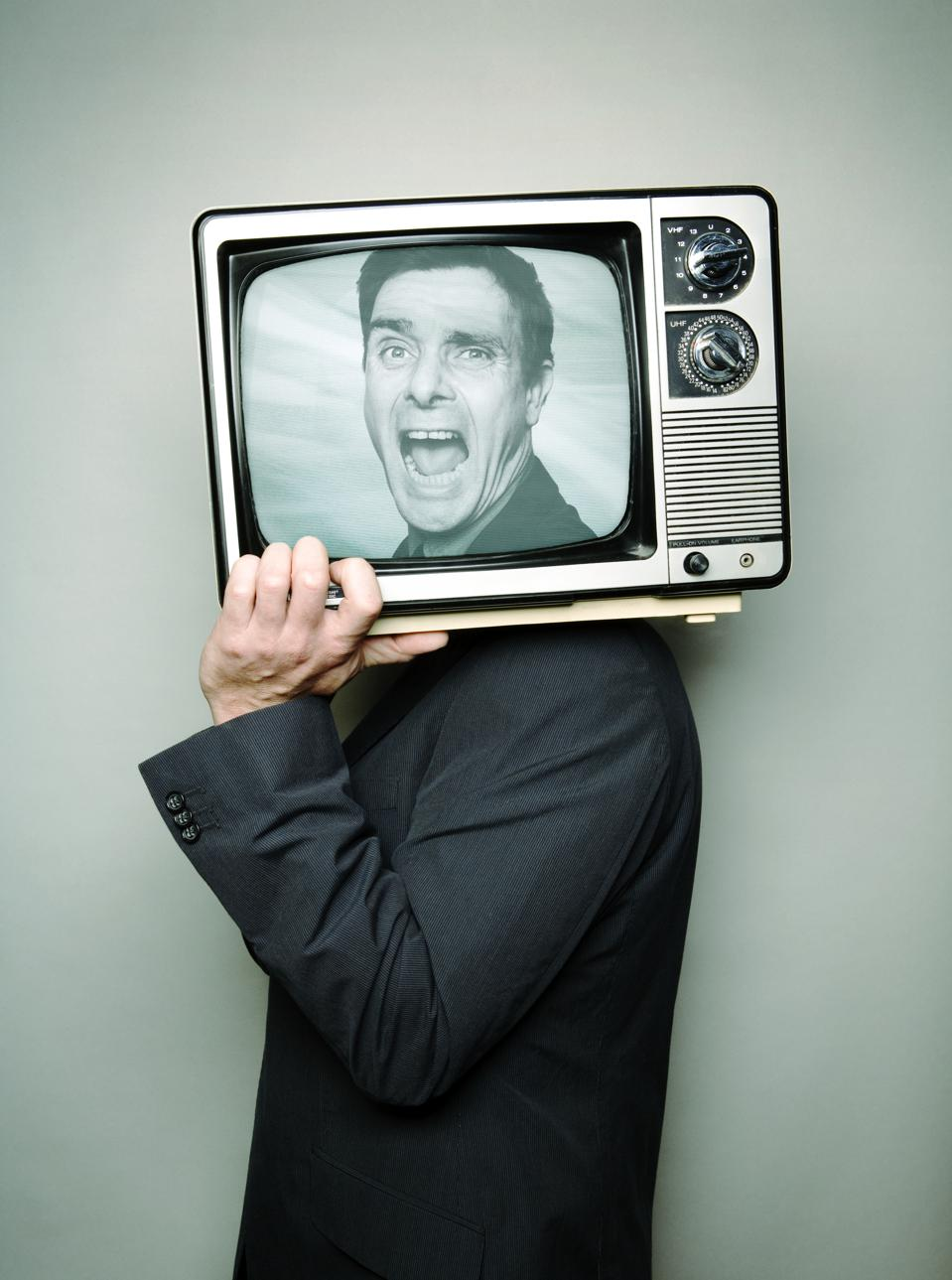 Businessman carrying television on shoulder, face on screen, shouting