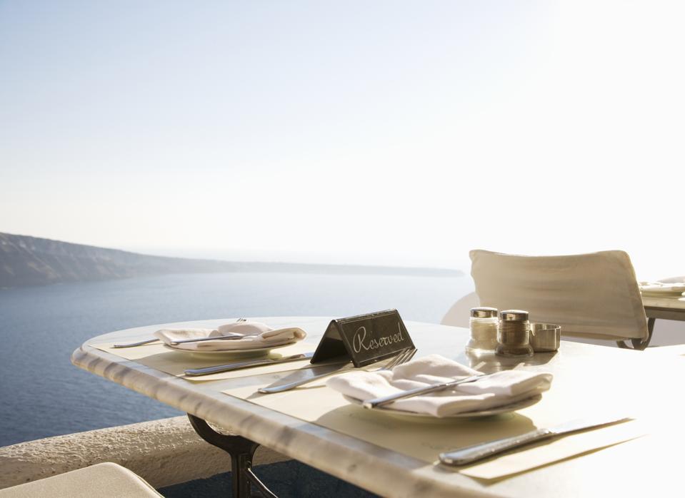 Greece, Santorini, Oia, reserved restaurant table overlooking sea
