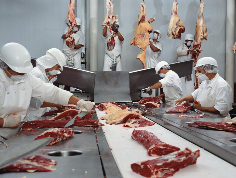 Meat plant workers wear masks on the line.