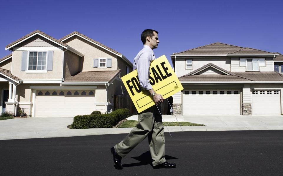 Male estate agent walking in front of house with holding for sale sign, side view