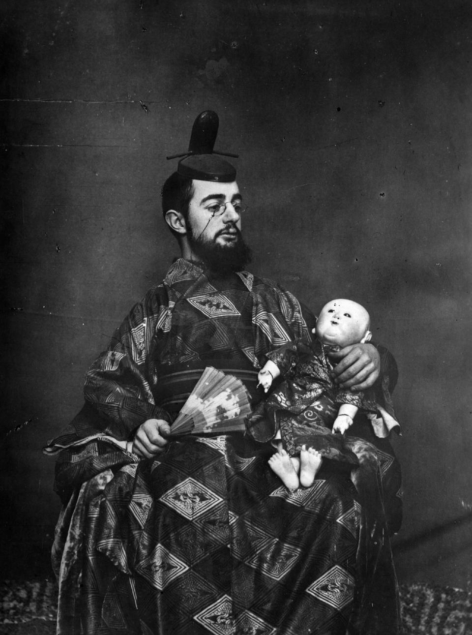 French painter Toulouse-Lautrec wearing Japanese fancy-dress costume and carrying a doll.