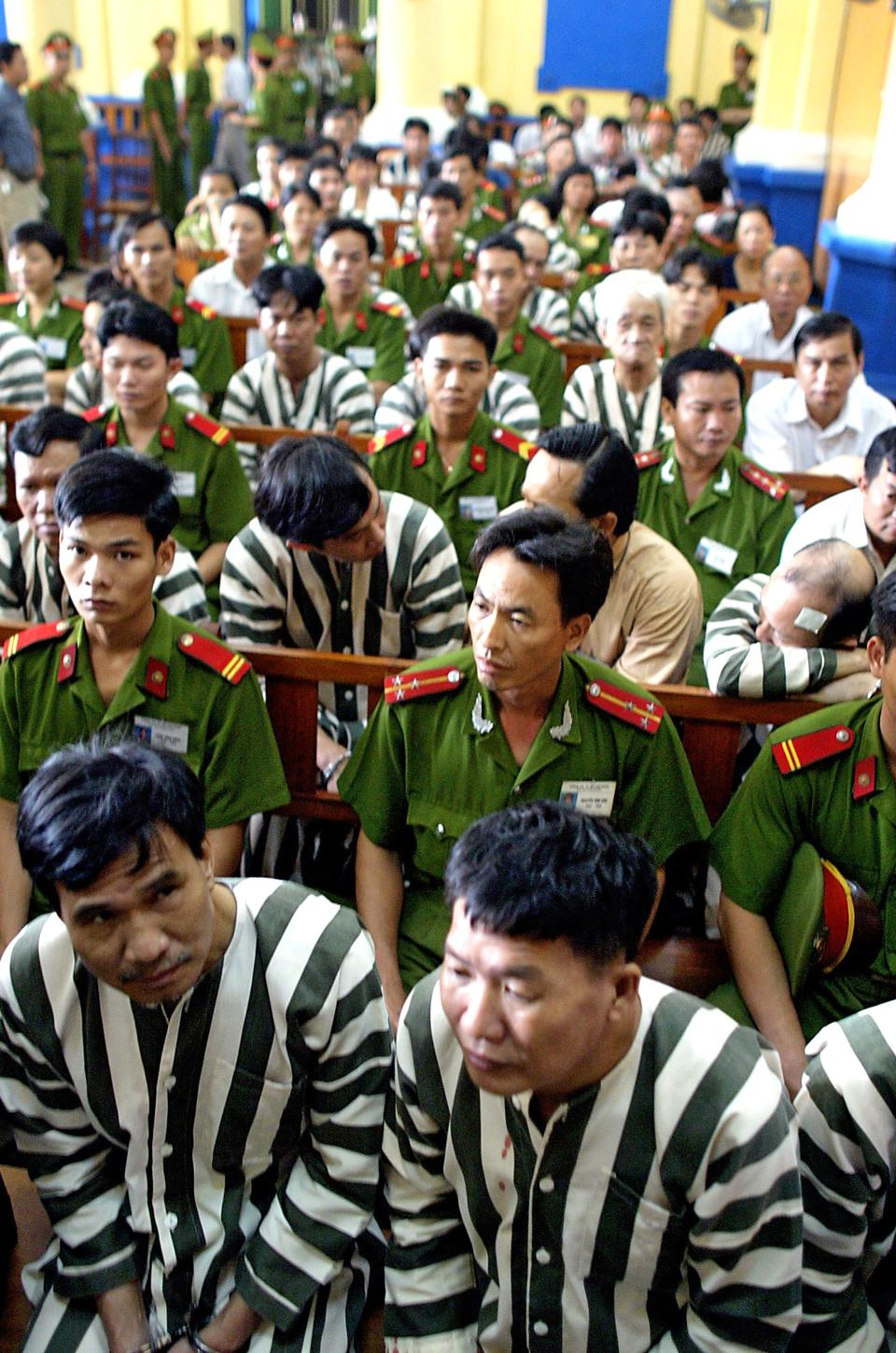 Defendants and police await a verdict during a corruption trial in Ho Chi Minh City's court in June 2003. (AP Photo/Richard Vogel, FILE)