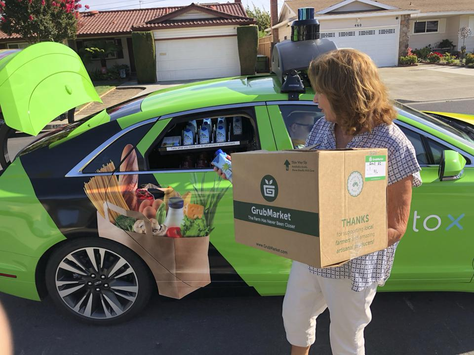 A woman unloads a GrubMarket grocery delivery from an AutoX self-driving car in San Jose, California.