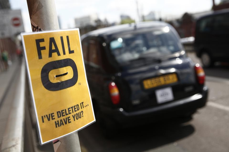 A black London taxi cab passes a poster protesting against the Hailo smartphone app outside Waterloo train station. Photographer: Simon Dawson/Bloomberg