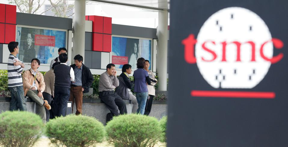 People take a rest behind the logo for Taiwan Semiconductor Manufacturing Co. (TSMC) at the company's headquarters in Hsinchu, Taiwan.